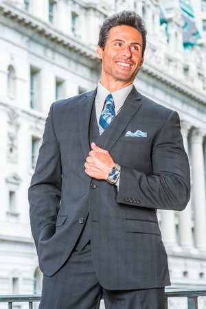 Way to Success. Dressing in dark blue three piece suit, necktie, wearing wristwatch, a handsome, sexy, middle age businessman is standing in the front of office building, confidently looking forward. Stock Photo