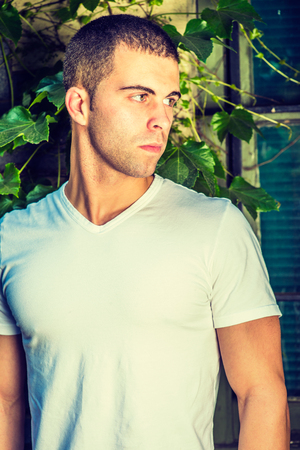 Portrait of young man, wearing a white V neck T shirt,  short hair.