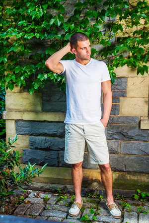 Young man thinking. Wearing a white V neck T shirt, light yellow shorts,  leather shoes, a hand scratching the back of head, a young guy is standing by a wall with green ivy leaves, waiting, thinking. Stock Photo