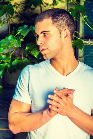 Portrait of young man, wearing a white V neck T shirt,  short hair, grasping hands Stock Photo