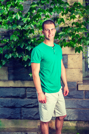 Portrait of young man. Wearing a green short sleeve Henley shirt, light yellow shorts, a young guy is standing by the wall with green ivy leaves, smiling, looking at you.
