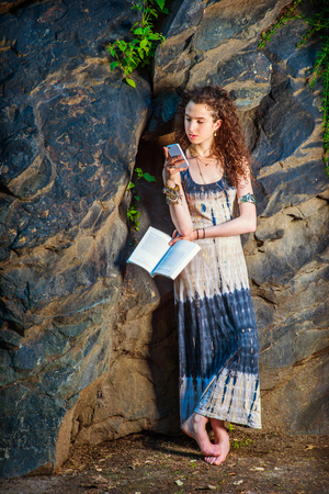 College Student. Dressing in long dress, chunky chain bracelet, arm cuff bracelet, barefoot, a teenage girl with curly long hair is standing against rocks, holding a book, texting on cell phone.