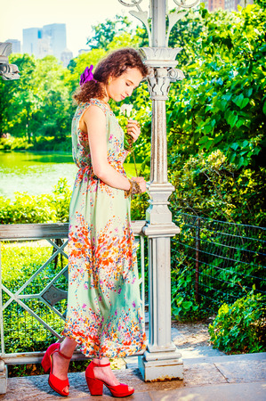 Lady Missing You at Park. Dressing in sleeveless, light green, long dress, red sandals shoes, pretty teenage girl standing inside pavilion, hand holding white rose, looking down, sad, thinking. Stock Photo