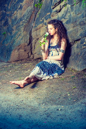 You in Memory. American teenage girl with curly long hair wearing patterned long dress, bracelet, barefoot, sitting on ground against rocky wall, holding white rose, closing eyes, smelling, thinking.