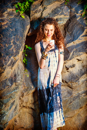 chunky: Dressing in long dress, chunky chain bracelet, arm cuff bracelet, a teenage college student with curly long hair is standing against rocks, hand holding a smart phone, smiling, reading, texting.