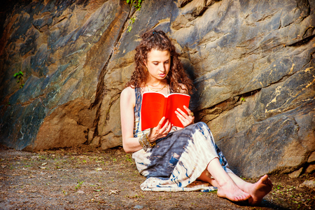 Girl Reading Outside. Wearing long dress, bracelet, barefoot, a pretty teenage college student with curly long hair is sitting on ground against rocks, holding a red book, reading, thinking, relaxing.