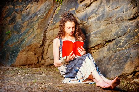 Meisje dat buiten leest. Het dragen van lange jurk, armband, op blote voeten, een mooie tiener college student met lang krullend haar zit op de grond tegen de rotsen, met een rood boek, lezen, denken, ontspannen. Stockfoto