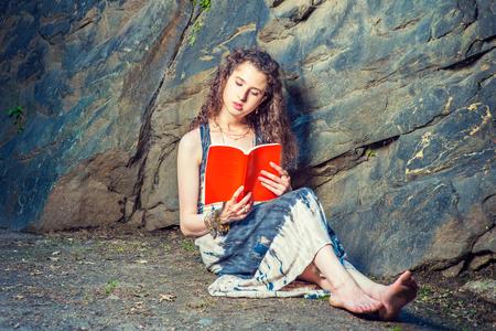 Ragazza che legge all'esterno. Indossando un vestito lungo, bracciale, a piedi nudi, uno studente universitario piuttosto giovane con i capelli lunghi e ricci è seduto a terra contro le rocce, tiene in mano un libro rosso, legge, pensa, si rilassa. Archivio Fotografico - 80557765