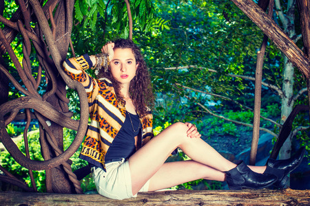 Dressing in black under wear, patterned fashion jacket, shorts, chunky chain bracelet, boot shoes, a teenager girl with curly long hair is sitting on wooden fence, looking at you, relaxing, thinking