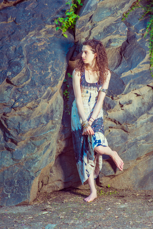 American Teenage Girl Summer Fashion in New York, with curly long hair, bare feet, wearing patterned long dress, chunky chain bracelet, arm cuff bracelet, standing against rocky wall, looking around.