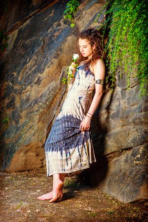 Meisje mist jou. Dressing in patroon lange jurk, armband, op blote voeten, een mooie tiener meisje met lang krullend haar staat tegen rotsachtige muur, met een witte roos, naar beneden, denken.