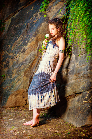 Girl Missing You. Dressing in patterned long dress, bracelet, barefoot, a beautiful teenager girl with curly long hair is standing against rocky wall, holding a white rose, looking down, thinking.