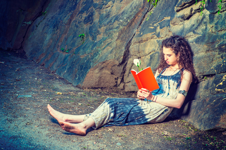 Girl Reading Outside. Wearing long dress, barefoot, a pretty teenage college student with curly long hair is sitting on ground against rocks, holding a red book and a white rose, reading, relaxing. Archivio Fotografico