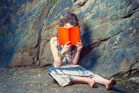 Girl Thinking Hard. Wearing long dress, bracelet, barefoot, a pretty teenage college student with curly long hair is sitting on ground against rocks, holding a red book covering her face, thinking.
