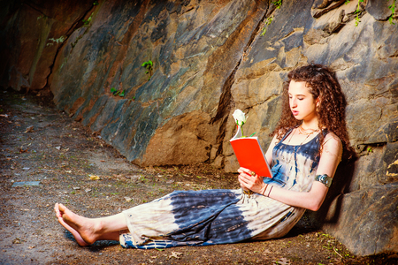 Reading Outside. Dressing in long dress, bracelet, barefoot, a pretty teenager girl with curly long hair is sitting on ground against rocks, holding a red book and a white rose, relaxing, reading.