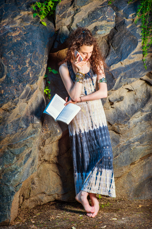 College Student. Wearing long dress, chunky chain bracelet, arm cuff bracelet, barefoot, teenage girl with curly long hair standing against rocks, holding book, looking down, talking on cell phone.
