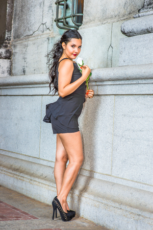 City Girl. Dressing in black, sleeveless top, short pants, high heels, a young pretty lady is standing by an old fashion wall, holding a white rose, turning back, charmingly looking at you.