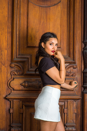 College Student. Dressing in black, short sleeve top, white short fit skirt, a young pretty lady with long curly hair is standing by an office door, a hand touching her chin, looking at you.