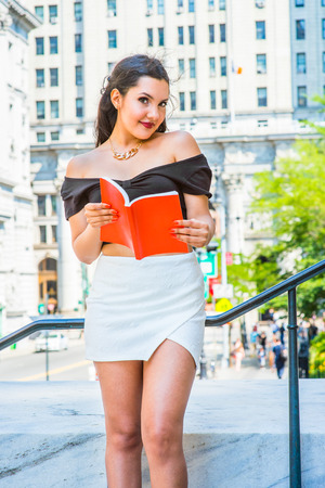 College Student. Dressing in black, short sleeve top, white short wrap skirt, a young pretty girl is standing by railing outside an office, holding a red book, charmingly looking at you. Stock Photo