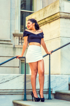 sleeve: College Student. Dressing in black, short sleeve top, white short wrap skirt, high heels, a young pretty lady with long curly hair is standing by railing outside an office, relaxing. Street Fashion Stock Photo