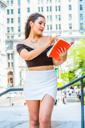 College Student. Dressing in black, short sleeve top, white short wrap skirt, a young pretty girl is standing by railing outside an office, looking down, finger turning pages, reading a red book.