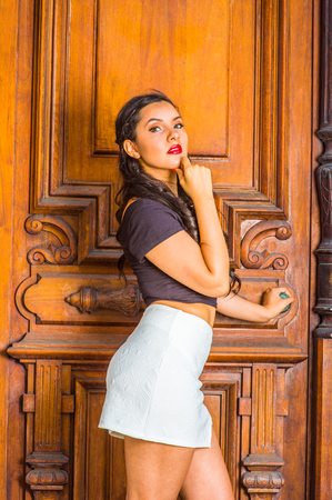 sleeve: Opening Wisdom Door. Dressing in black, short sleeve top, white short fit skirt, a young pretty lady standing by library door, a hand touching her chin, a hand holding knob, confidently looking up.