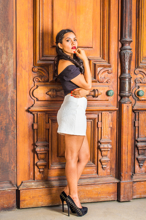 American college student with long curly hair wearing black, short sleeve top, white short fit skirt, high heals, standing by vintage office door on campus in New York, hand touching chin, thinking.