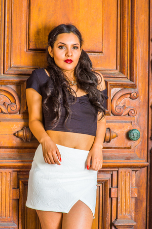 Girl waiting for you. Dressing in a black, short sleeve top, white short fit skirt, a young pretty lady with long curly hair is standing by an old fashion style door, charmingly looking at you.