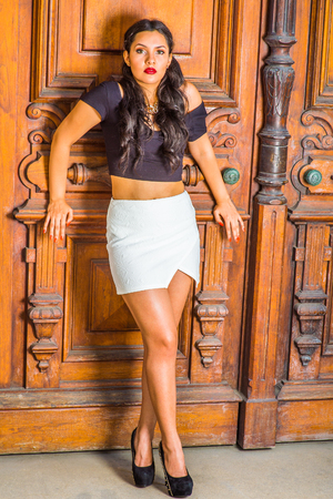 Fashion Girl. Dressing in black, short sleeve top, white short wrap skirt, high heels, a young pretty lady with long curly hair is standing by an office door, charmingly looking at you.