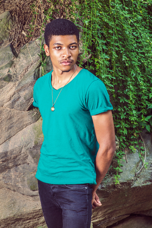 sleeve: Portrait of Young Black Man. Wearing a green, short sleeve, V-neck T shirt, necklace, black pants, a young handsome guy is standing by rocks with green leaves, hands in the back, looking at you.