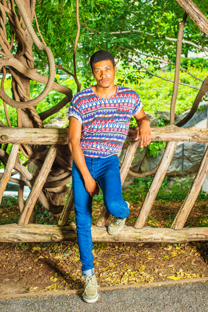 Young Black Man Waiting for You. Wearing a colorful pattern shirt, blue jeans, sneakers, necklace, a young handsome guy is standing against a wooden fence, charmingly looking at you.