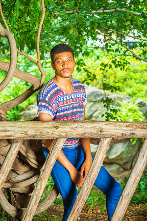 Young Black Man Waiting for You. Wearing a colorful pattern shirt, blue jeans, sneakers, necklace, a young handsome guy is sitting behind a wooden fence, charmingly looking at you. Stock Photo