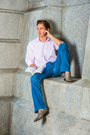 sleeve: Leisure Time. Wearing a light pink, long sleeve shirt, blue jeans, leather shoes, a young guy is casually sitting against a concrete wall, reading a book, making a phone call on his cell phone. Stock Photo