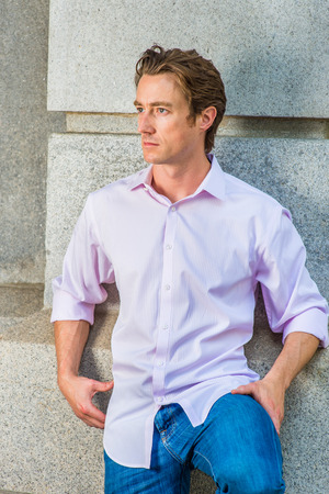 sleeve: Man Thinking Outside. Wearing a light pink, long sleeve shirt, blue jeans, bending a leg, a young handsome guy is standing against a concrete wall, looking around, thinking