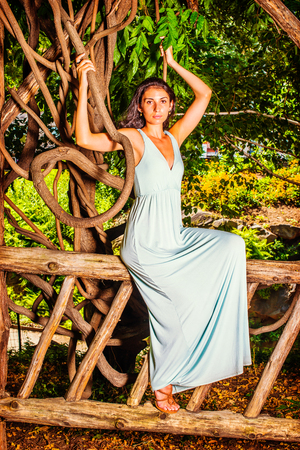 Portrait of Pretty Lady. Dressing in a light blue long dress, a young woman with long curly hair is sitting on wooden fence, raising arms, holding branches of rattan, looking at you.