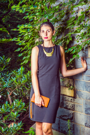 Working Woman Fashion. Dressing in black work dress, a necklace with golden pendant, holding small brown purse, a young sexy businesswoman is standing against a wall with ivy leaves, looking forward.