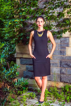 Lady wacht op jou. Dressing in zwarte werkkleding, een ketting met gouden hanger, leren schoenen, een jonge sexy vrouw staat buiten tegen de muur met groene klimopblaadjes, kijkend naar voren. Stockfoto