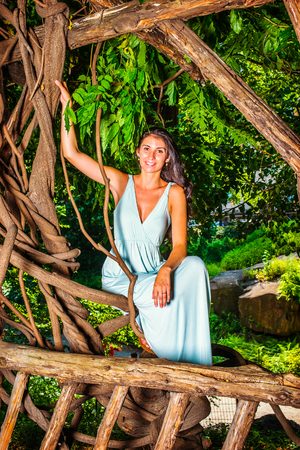 Pretty Lady Relaxing Under Trees. Dressing in a light blue long dress, a young woman with long curly hair is sitting under trees, smiling, happily looking at you.