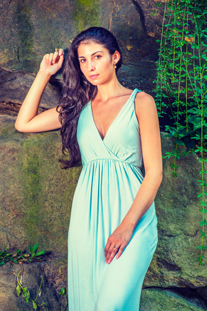 Portrait of Pretty Lady. Dressing in a light blue long dress, a young sexy woman with long curly hair is standing by rocky wall with long green leaves,  charmingly looking at you.