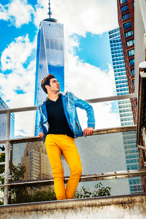 Looking for Success. Dressing in blue jacket with hood, black under wear, yellow pants, a young handsome guy is standing in the front of high tower building, confidently looking forward. Stock Photo