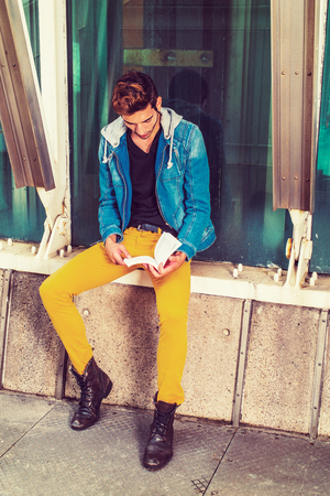 Man Reading Outside. Dressing in a blue jacket with hood, black under wear, yellow pants, leather boot shoes, a young handsome guy is sitting by a metal structure, against a glass wall, reading a book. Imagens