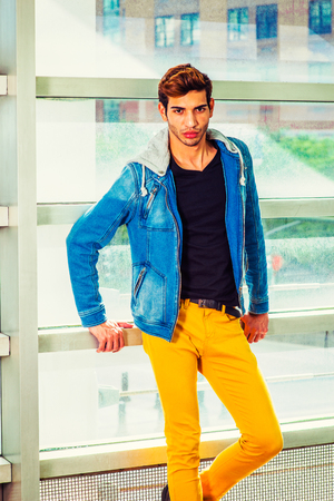 College Student. Dressing in a blue jacket with hood, black under wear, yellow pants, a young handsome guy is standing against a glass wall, confidently looking at you.