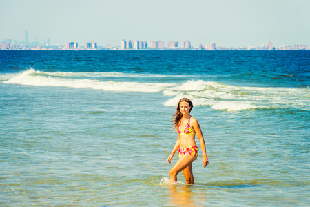 Girl Wading on Water. Wearing a red, yellow patterned two piece bikini bathing suit, a young pretty woman is walking in water on the beach, confidently looking forward. The background is New York.