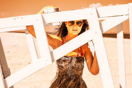 Woman's Beauty. Wearing sunglasses, dressing in a dark blue sundress, raising a arm, looking through a wooden structure, a young pretty girl is standing on beach, waiting for you. Vintage effect.