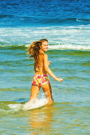 Happy Girl Wading on Water. Wearing a red, yellow patterned two piece bikini bathing suit, a young woman is running in water on the beach, smiling, looking back, hair floating with wind. Instagram filtered look. Reklamní fotografie - 87170510