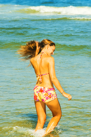 Girl Wading on Water. Wearing a red, yellow patterned two piece bikini bathing suit, a young woman is walking in water on the beach, lowering her head, hand managing hair. Instagram filtered look.