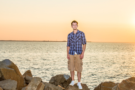 Man Waiting for You on Sunset. Wearing white, blue patterned shirt, yellow pants, white sneakers, a young handsome guy is standing on rocks by a bay, looking forward.
