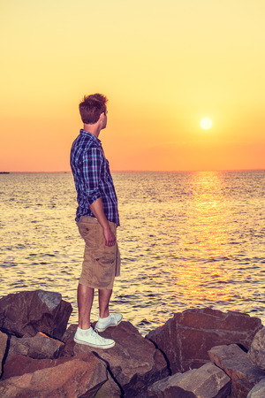 Man Watching Sunset in Back View. Wearing white, blue patterned shirt, yellow pants, white sneakers, a handsome guy is standing on rocks on beach, looking at horizontal of ocean, waiting for you. Reklamní fotografie