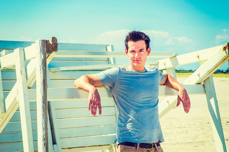 Man waiting for you. Wearing a gray t shirt, arms resting on a wooden stick, a young handsome guy is standing by a wooden structure on the beach, narrowing eyes, charmingly looking at you.