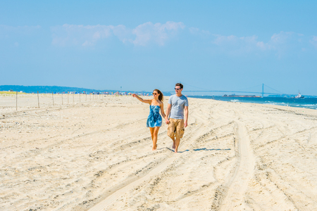 shorts t shirt sexy: Young couple walking on the beach. Wearing sun glasses, holding hands, guy wearing gray t shirt, yellow pants, girl dressing in strapless blue sun dress, raising an arm, finger pointed distance place.